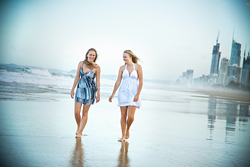 Outdoor family photo of 2 sisters on the beach with the Gold Cast skyline as a stunning backdrop